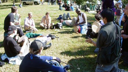 A group sits on the grass north of the reflecting pool, playing real drums, as well as tambourines.