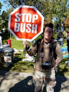 """This woman simply holds up a stop sign, reading """"STOP BUSH""""."""