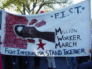 A large banner carried by some marchers, with the theme FIST: Fight Imperialism, Stand Together.