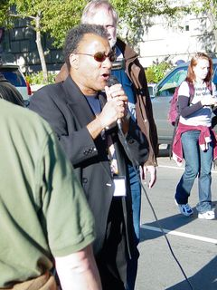 Larry Holmes stands in front at the microphone, leading the group.