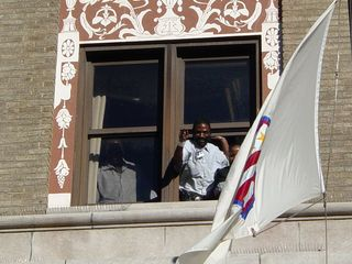 Three Hotel Washington employees lean out of a third-story window, lending support to our efforts to support them. Based on the expressions on their faces, you could tell that these workers were glad to see us coming.