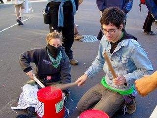 Meanwhile, Jess and others make sound on their makeshift drums.