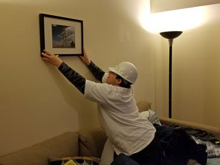 Elyse removes a photo of the Washington Monument, creating another bare wall.