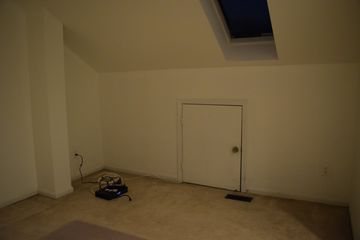 A near-empty mezzanine, with only a chair mat, a cable box, and a future wallhanging in the room.