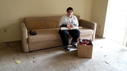 Elyse sits on the couch, without the cushions. The couch was the last piece of furniture to leave.