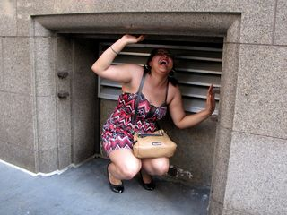 """In our hunt for a subway station, Doreen found this little alcove in a building wall, and posed with it. The first pose was with a smile, and then the second one was sort of a """"trapped"""" pose."""