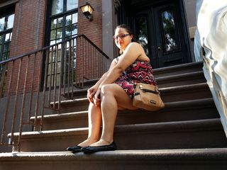 Doreen poses for a photo on the front steps of the Cosby Show house.