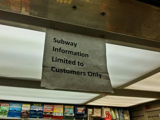 """As we made a transfer, we spotted this sign on a vendor's stand in the subway system: """"Subway information limited to customers only"""". I guess, with his being located in a very busy (and complex) part of the subway system, a lot of questions about the subway come with the territory."""