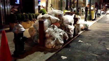 Bagged trash piled up in front of the aforementioned Hilton Garden Inn.