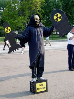 """In addition to the four """"prisoners"""" in costume, another person wore a black robe, a rubber skeleton mask, black gloves, and holding cardboard cutouts designed to look like nuclear weapons, while standing on a crate containing a sign saying """"NO NUKES"""". And on top of that, a woman wore a black costume with red wings and gloves, and carried a three-pronged fork, to represent the devil."""