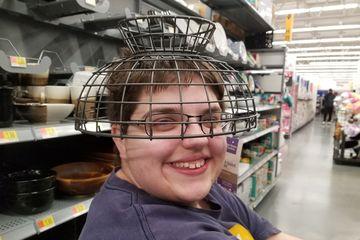 Elyse wears a fruit basket on her head at Walmart.