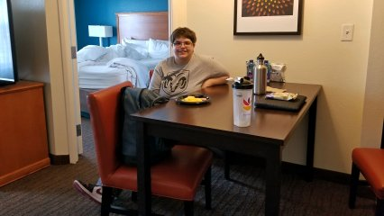 Elyse sits at the table in our room at the Residence Inn with her breakfast, which was a full-on hot breakfast where you served yourself, which I was kind enough to bring up for her.