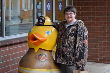 Here, Elyse poses for a photo with a duck sculpture, where the duck is dressed as a firefighter.