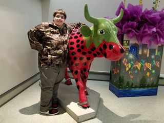 """Elyse poses with """"Strawberry Cow"""" at Strawberry Square in downtown Harrisburg. This statue is from the """"Cow Parade"""" event that occurred in Harrisburg in 2004."""