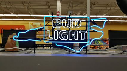 """Neon """"Bud Light"""" sign with the outline of North Carolina on it in the beer aisle, along with a bunch of others advertising various brands. Walmart stores in Maryland don't sell alcohol, and Virginia stores don't have this sort of display, so this was certainly a novelty. I can't say that I'm jealous, either, as I've always thought that neon beer signs were tacky."""