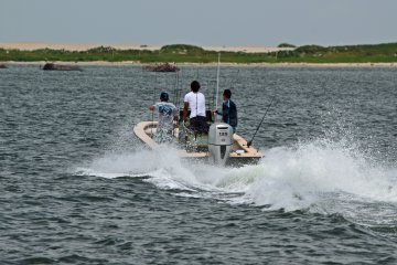 Three people riding a powerboat, presumably on their way to go fishing.