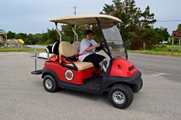 Elyse drives the golf cart.