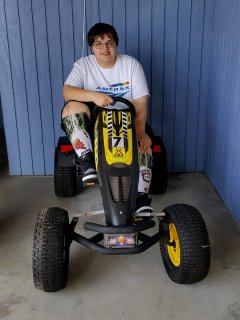 Elyse sits on some sort of all-terrain pedal vehicle at the KOA.