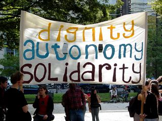 """A few large banners stood out in the crowd, such as this one stating """"Dignity, autonomy, solidarity""""."""