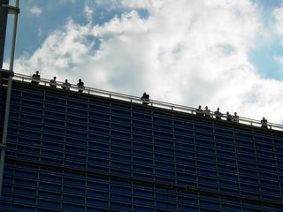 All the while, a number of people watched from the roof of the World Bank. Seems that skin got their attention. One man, at center, was even filming...