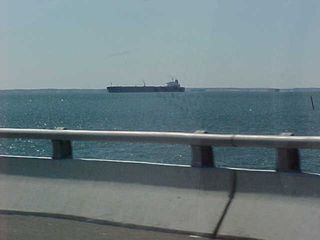 A ship is visible off in the distance on the bridge-tunnel...
