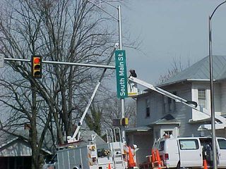 While running an errand in Harrisonburg, I caught workers putting up the new street signs that got featured inThe Breeze in the first issue after Spring Break.  I'm afraid this is a much better picture than what was in The Breeze because this shows them actually putting the sign up...