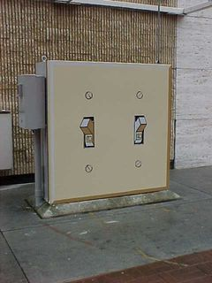 This electrical box certainly has an interesting paint job, designed to look like light switches.  However, the aspect is a bit odd, with the switches facing opposite directions.