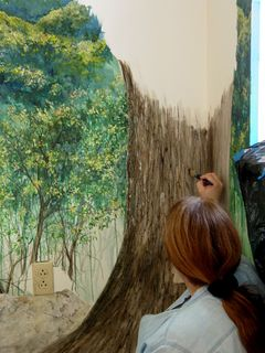 Inside, a woman makes the Discovery Center beautiful with a new mural on the wall.