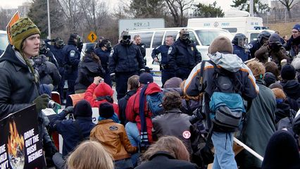 Meanwhile, we were basically at an impasse with the police. Neither side was about to back down. The seated black bloc stood their ground, and the gas-masked cops held theirs.