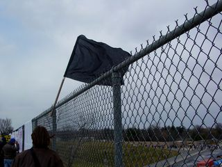 A black flag flew from another fence.