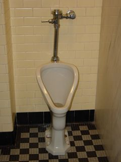 Vintage urinal, seen in 2016 (at left) and from my previous visit in 2003 (at right, different location in the church). Except for the automatic flusher, it is unchanged.