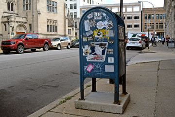 Mailbox covered in stickers, across Baum Blvd. from the church.