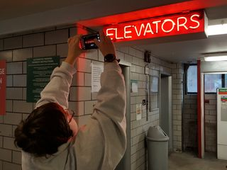 """Elyse gets a photo of the neon """"ELEVATORS"""" sign on the first floor."""