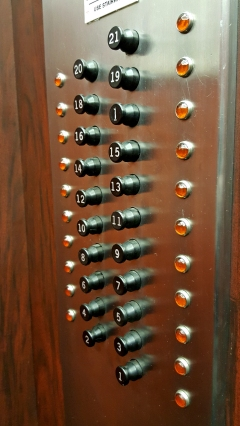 Buttons on the Investment Building elevator, with pop-out buttons and indicator lights to the sides of the buttons. The first floor is selected in the left photo.
