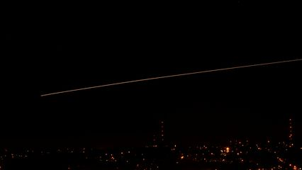 Airplane flying over the city, captured with a 30-second exposure.