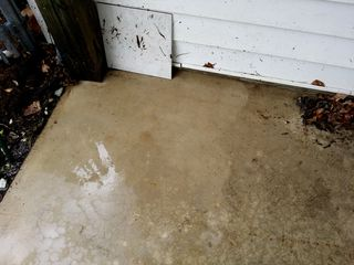 Southwest corner of the carport floor after washing began. This corner was the most protected of the four, as it is against the house and near the shed, plus a trash can normally sits in this corner. However, there is still a noticeable difference between cleaned and not cleaned.
