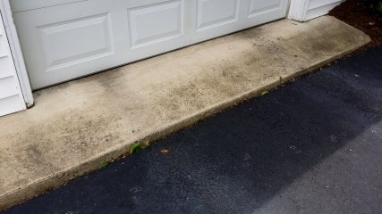 The driveway edge before cleaning, with a whole bunch of gunk on it.