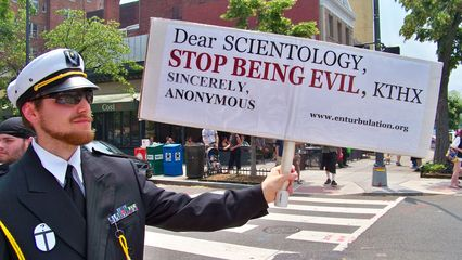 """John McNonymous, dressed in a manner resembling a naval dress uniform, holds a sign saying, """"Dear Scientology, stop being evil, KTHX. Sincerely, ANONYMOUS."""""""