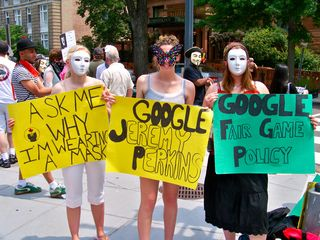 """Three women hold three signs. """"Ask me why I'm wearing a mask"""" is a common sign since Anonymous wears masks to their protests (since Scientology is known to retaliate against their critics), """"Google Jeremy Perkins"""" refers to a person who ultimately flipped after his mother used Scientology treatments to help his mental illness, and """"Google Fair Game Policy"""" refers to Scientology's practice of """"Fair Game"""" as described above. Unlike many other protest groups I've demonstrated with, rather than simply displaying URLs, many Anon signs encourage people to do their own research, inviting them to use Google to search for the terms that get mentioned."""