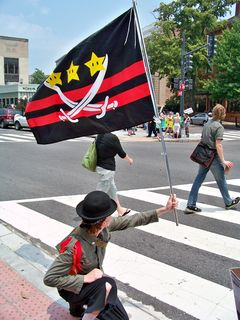 Wutman holds up a flag that Anonymous DC created specifically for this raid. It combines elements of the Sea Org emblem with elements of the flag of the District of Columbia.
