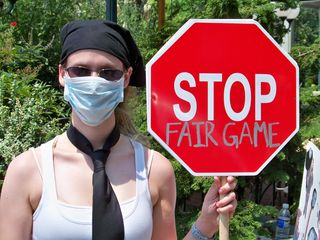 """A woman wearing a necktie and a surgical mask holds a sign saying """"STOP FAIR GAME""""."""