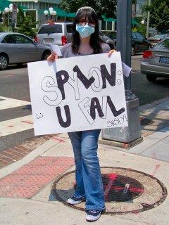 "Another Anon holds the ""SPYLON: U FAIL"" sign."