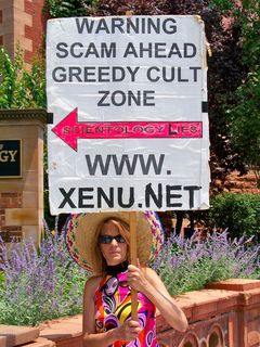 This woman holds a sign with an arrow pointed directly at the Org.