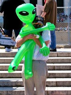 An Anon hugs an inflatable Xenu.