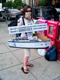 At the flash raid back at the Org, one Anon wears the cruise ship Freewinds while holding a sign questioning why a church would need to own a cruise ship.
