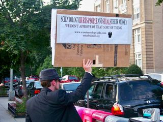 Meanwhile, John McNonymous holds a sign towards the Org.