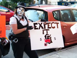 """AnonGurl holds up a sign: """"EXPECT IT"""", referring to """"Project Five""""."""