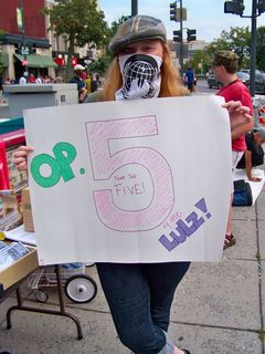 Another Anon holds a Project Five sign.