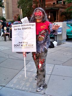 """With a new twist on the lighted-eyes theme, this Anon dressed as a zombie, with a sign saying, """"I joined Scientology for the BRAINS... but they DON'T HAVE ANY."""" The shirt says """"Billion year contract"""" on the front, and """"Die-enetics: Get it... read it... brainwash it!"""" on the back."""