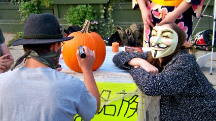 Drawing the Guy Fawkes face on the pumpkin.